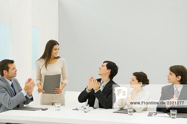 Geschäftsfrau steht neben Konferenztisch  hält Dokument  Kollegen schauen sie an und klatschen