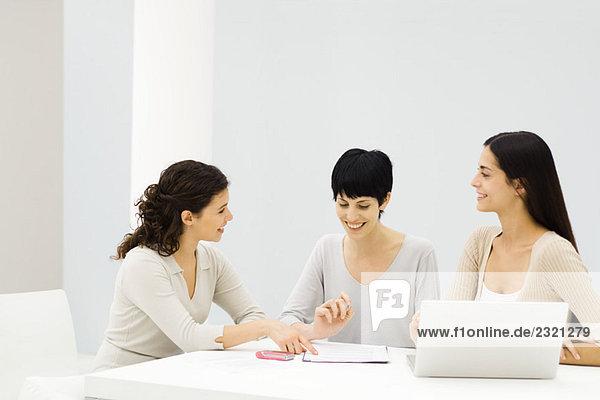 Drei Geschäftsfrauen sitzen am Tisch  diskutieren Dokument  lächeln