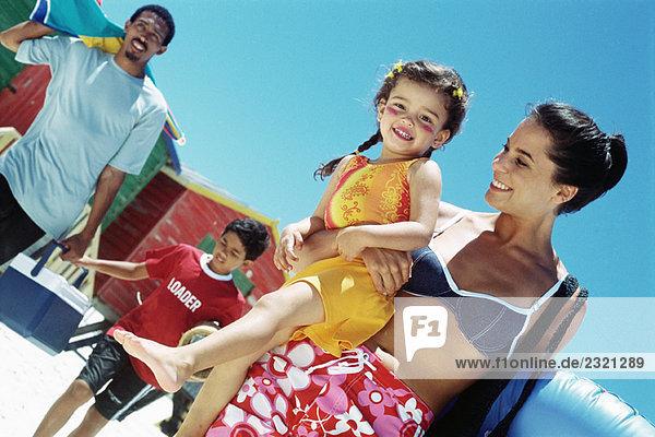 Familie geht am Strand spazieren  Mutter trägt Tochter  Mädchen lächelt vor der Kamera