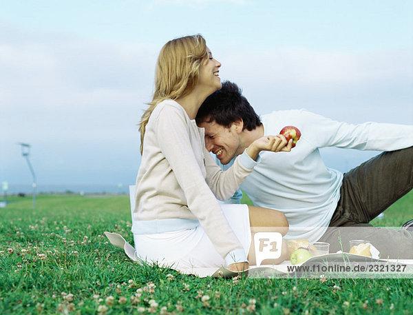 Paar auf Picknickdecke sitzend  lachend  Frau mit Apfel haltend