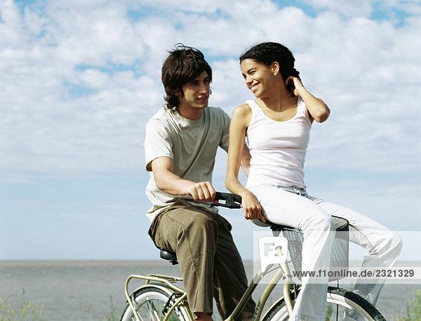 Junges Paar auf dem Fahrrad  Frau auf dem Lenker sitzend  über die Schulter schauend