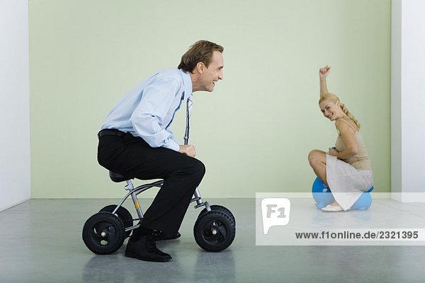 Mann auf dem Kinderfahrrad  Frau lächelt vor der Kamera im Hintergrund