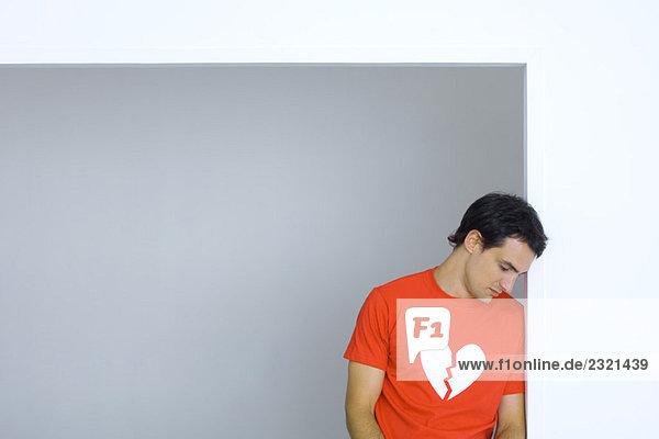 Mann im T-Shirt mit gebrochenem Herz-Symbol  Blick nach unten