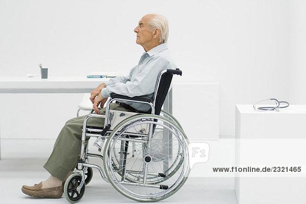 Älterer Mann im Rollstuhl in der Arztpraxis  Seitenansicht