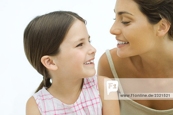 Mother and daughter smiling at each other  close-up