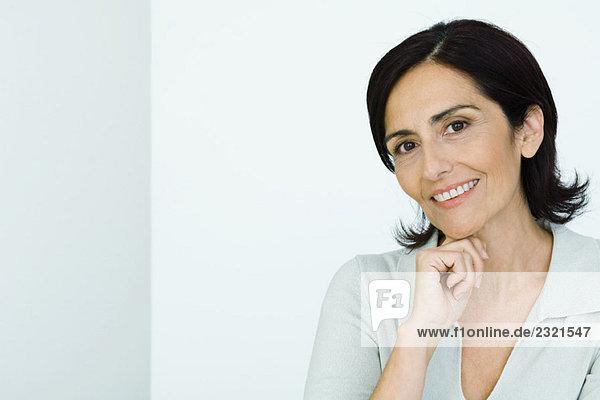Reife Frau  Hand unter dem Kinn  Kamera lächelnd  Portrait