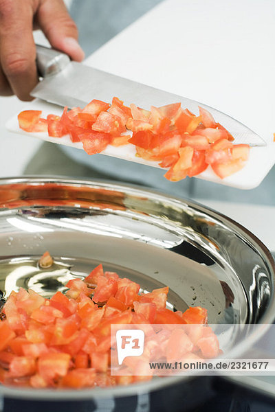 Man scraping diced tomatoes into saucepan with knife  cropped view