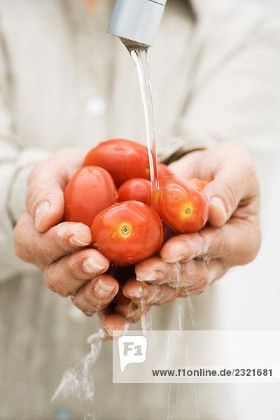 Frau spült eine Handvoll Tomaten unter dem Wasserhahn  Blick auf die Hände abgeschnitten