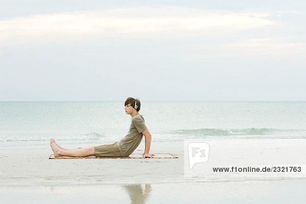Teenage boy sitting on the beach  listening to headphones  side view