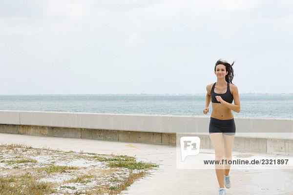 Junge Frau am Strand  Lächeln in die Kamera  Ganzkörperansicht