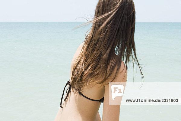 Junge Frau im Bikini am Strand  Horizont  Seitenansicht betrachten
