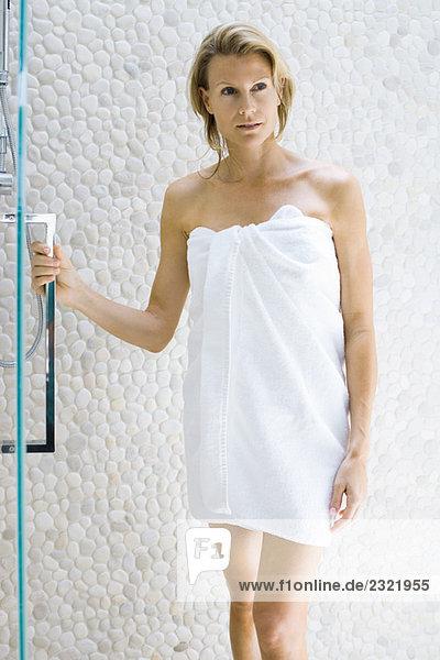 Woman in towel standing next to shower  holding onto door handle  looking away