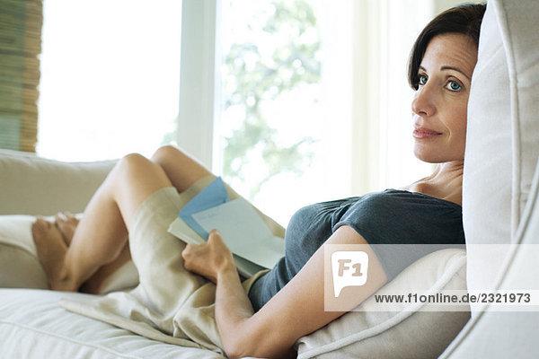 Frau sitzt auf Sofa  Buch und Briefpapier  hält  Wegsehen
