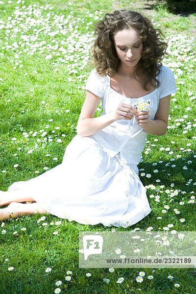 Junge Frau sitzend auf Wiese  Blumen  erhöhte Ansicht hält
