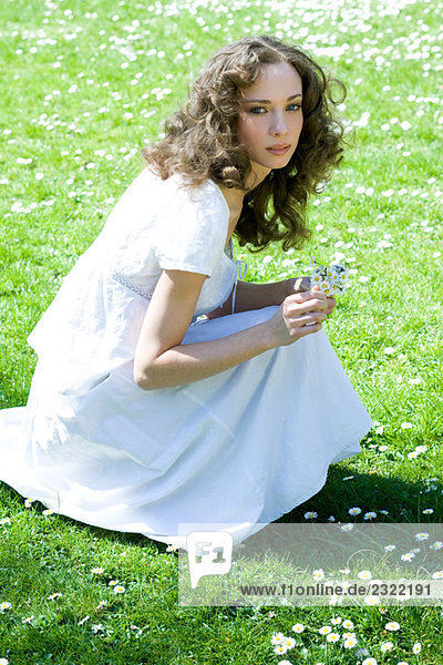 Junge Frau im Wiese  hocken pflücken Blumen  Blick in die Kamera bis