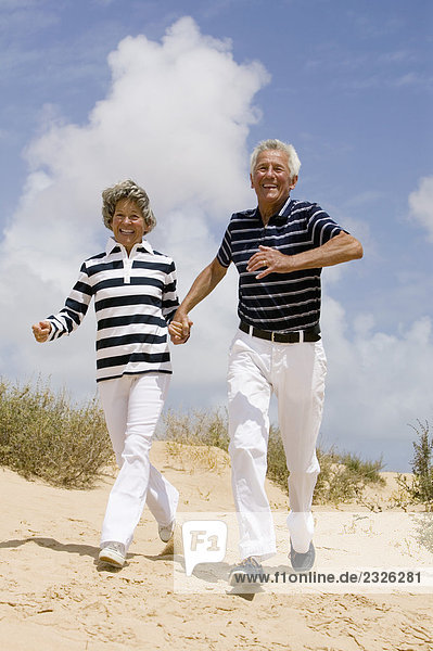 full body portrait of mature couple walking hand in hand on sandy beach