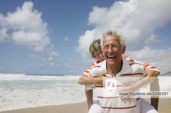 älterer Mann  Frau eine piggyback ritt auf Strand