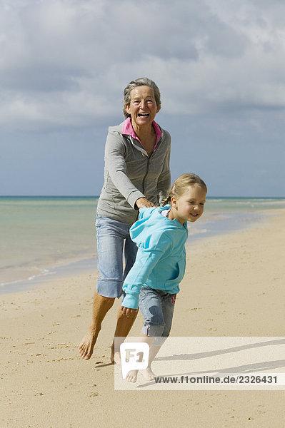 Reife Frau und Enkelin Spaziergang Strand