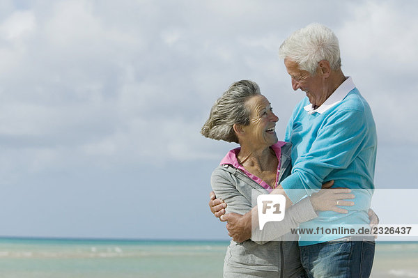 reifes Paar umarmen am Strand