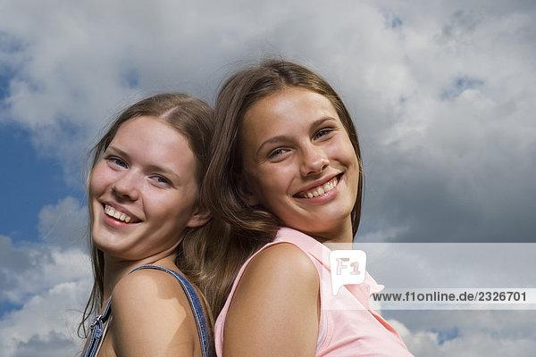 Kopfschuss von zwei junge Frauen Rücken an Rücken stehend lächelnd