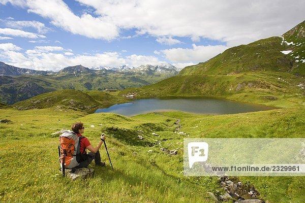 Rückansicht des Wanderer sitzen auf Felsen im Feld  Hohen Tauern  Salzburg  Österreich