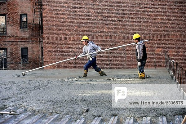 Bauarbeiter Glättung Beton mit lange float