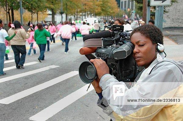 Schwarze Frau mit Handy und Hut