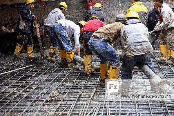 Bauarbeiter mit konkreten Pumper Schlauch pouring Betonboden