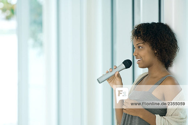Young woman singing into microphone  looking away