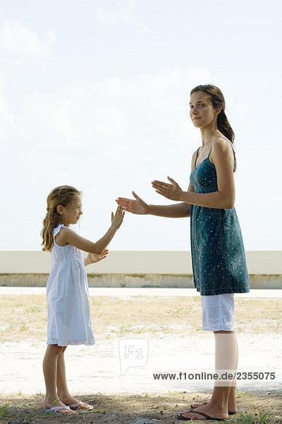 Junge Frau im Freien stehend  klatschend mit kleiner Schwester  lächelnd vor der Kamera