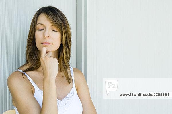 Frau mit Hand unter dem Kinn  Blick nach unten  Augen halb geöffnet