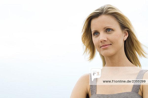 Blonde Frau lächelt  Haare blasen im Wind  Kopf und Schultern