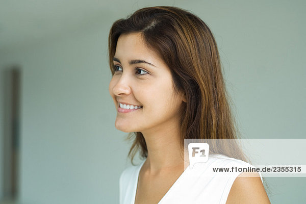 Young woman smiling  looking out of frame  head and shoulders  portrait