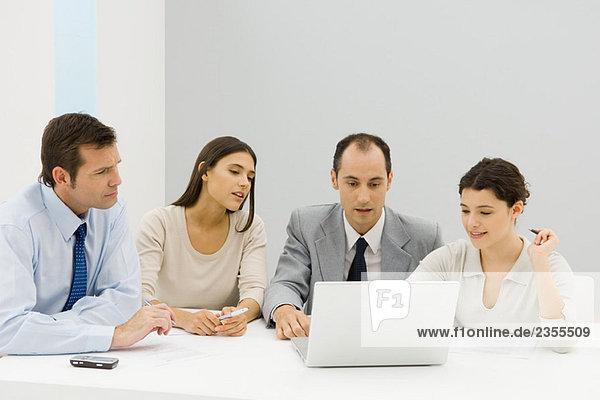 Team von Geschäftspartnern  die gemeinsam im Büro auf den Laptop schauen