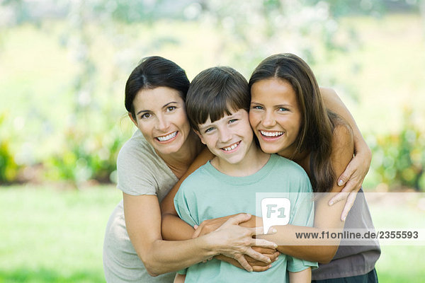 Mother with son and teenage daughter  smiling at camera  portrait