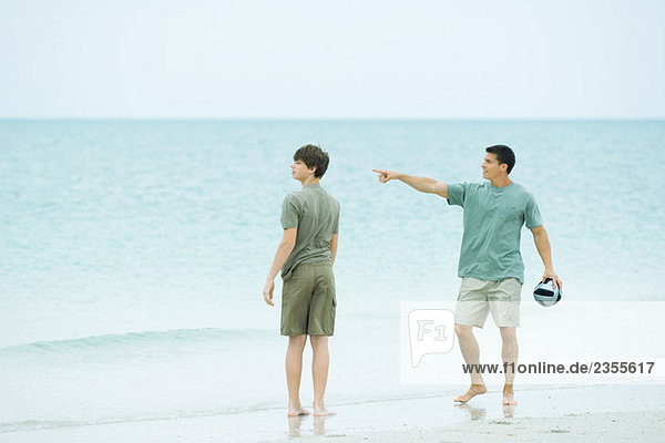 Father and teen son at the beach  man holding ball and pointing  both looking away