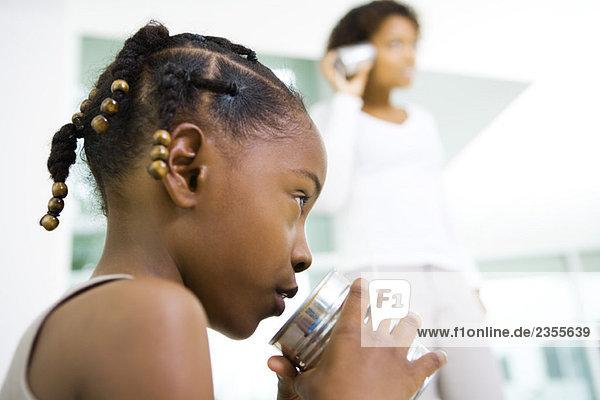 Kleines Mädchen  das in die Blechdose spricht  Mutter  die im Hintergrund zuhört  Blick in den niedrigen Winkel