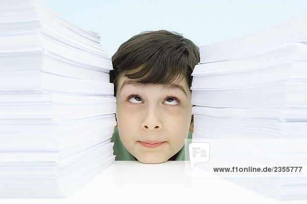 Boy resting head on table between two stacks of paper  rolling eyes