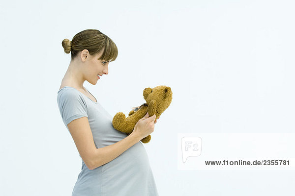 Pregnant woman holding teddy bear  smiling  side view