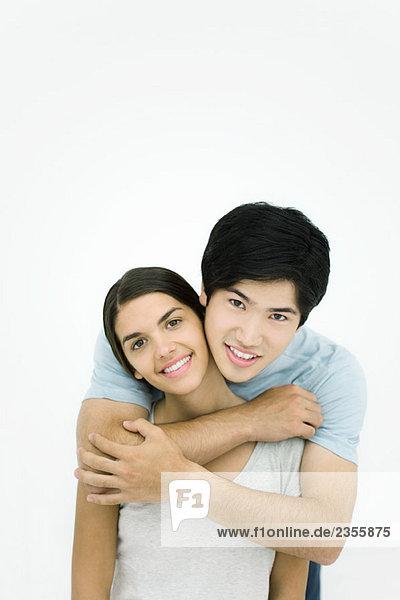 Junges Paar  Mann umarmt Frau von hinten  lächelnd vor der Kamera  Porträt