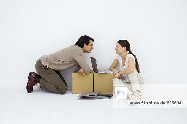 Ein Paar sitzt am Behelfstisch mit einem Laptop dazwischen und lächelt sich an.