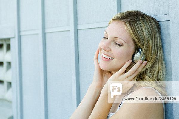 Woman listening to earphones  smiling