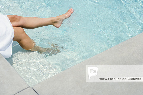 Woman sitting by swimming pool  soaking feet in water  cropped view