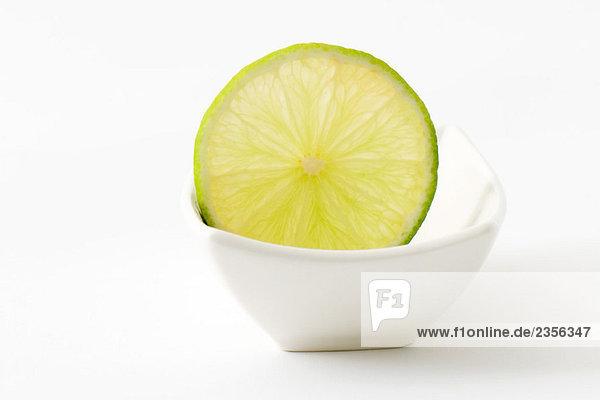 Slice von Kalk in kleinen Teller Slice von Kalk in kleinen Teller