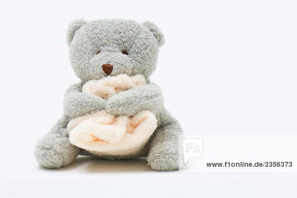 Teddy bear holding blanket