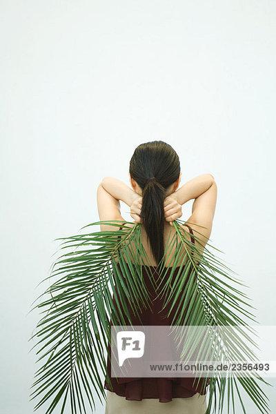 Palmenblatt hinter Rückansicht Frau halten