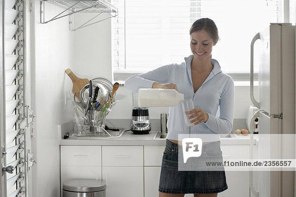 Frau in der Küche Milch in ein Glas gießen