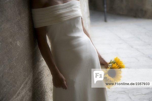Braut hält ein Bouquet von Sonnenblumen