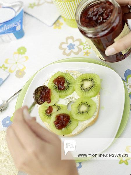 Nahaufnahme der person's Hand Scheiben Kiwi Fruit Jam anziehen