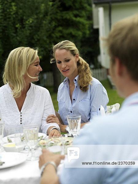 Zwei Frauen am Gartentisch Lächeln